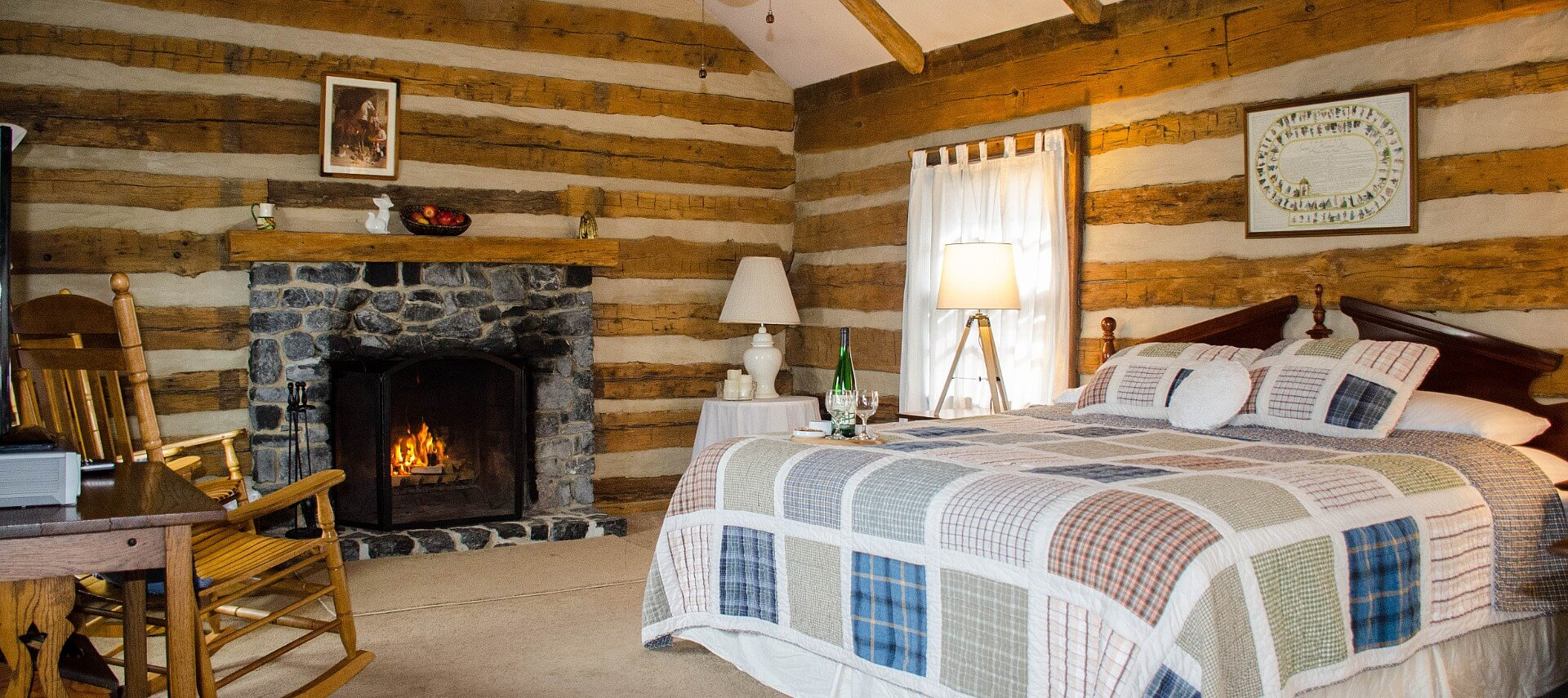 A log cabin room complete with a queen bed, window with white curtains, desk and chair, and a dark grey stone fireplace.