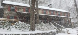Large two story log cabin house with snowing covering the surfaces and snow falling