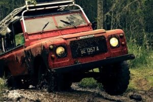 Red 4x4 vehicle driving through mud