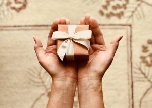 hands holding a small brown gift box with cream bow