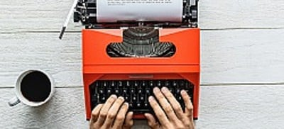 Two hands on red-orange typewriter with white paper and black print, next to white mug of black coffee on liight gray panelled table.