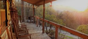 Large wooden porch with three wooden rocking chairs facing panoramic view of green trees and brilliant yellow setting sun.