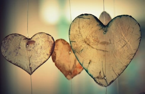 Three heart shaped wooden wind chimes against soft peach and green background.