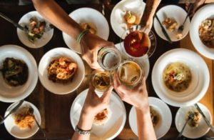 Four people clinking glasses together over numerous white bowls filled with various kinds of food on a brown table.
