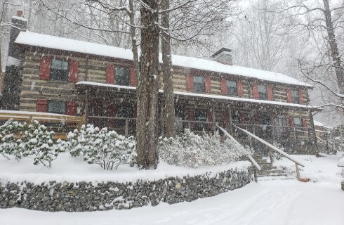 Snow covered two story log cabin house with burnt sienna shutters, large wood front porch with long set of stairs.