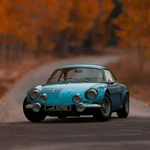 classic blue sports car with blurred autumnal background